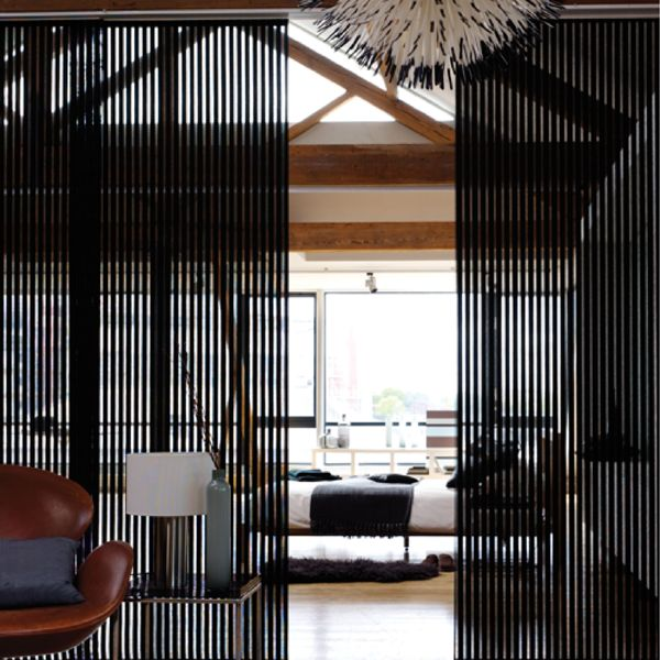 Panel blind is the most innovative shading solution for larger windows and patio doors. This blind also looks stunning as a stylish room divider. Here in black colour as a room divider. Illumin8 panel blind is available in a diverse range of designs and fabrics including, sheer voiles and faux suede, all of which will enhance the decor of any room.