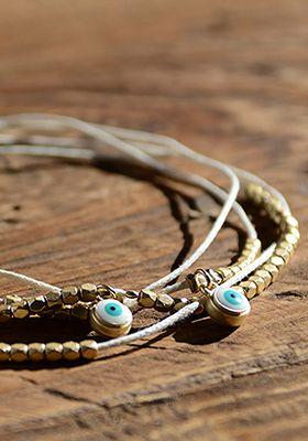 """Evil Eye bracelet-36"""" long white wrap around bracelet. Brass & wax cord. Can be worn as necklace. Can be adjusted by cutting and re-knotting end loop."""