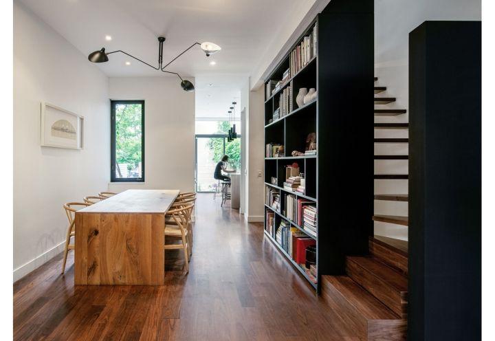 Ampie librerie nere anche per la zona living, definita da un tavolo rettangolare in legno di larice, disegnato su misura. http://www.elledecor.it/architettura/toronto-canada-ristrutturare-villa-vittoriana-d-epoca-green-Contrast-House-studio-architettura-Dubbeldam#5
