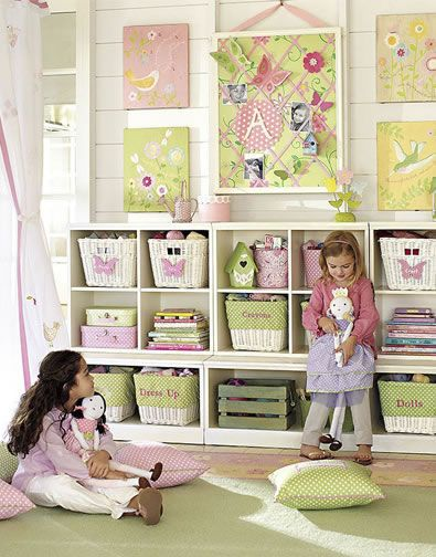 Lots of bright colors and a cheerful garden theme make this playroom inviting and sweet. We hung an airy tulle canopy from the ceiling to create a magical room within the room. A ribbon pinboard lets kids display their favorite photos and artwork without the use of tacks. For easy organization, we customized the low, accessible cubby-style storage system with baskets that have personalized liners.