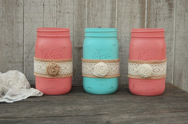 3 quart size mason jars hand painted in coral and aqua with a ribbon of burlap and lace, and a burlap flower, lightly distressed with a protective coating. They are not painted on the inside and can h