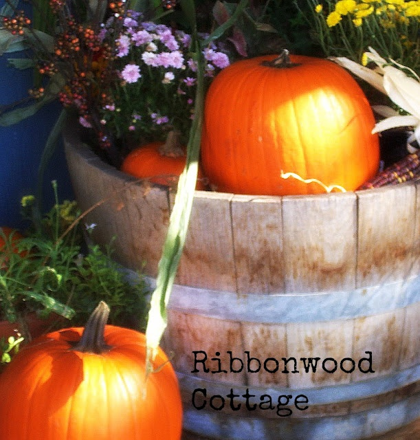 Wine barrel filled with mums and pumpkins