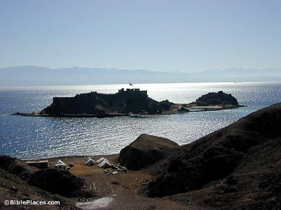 Pharaoh's Island, Coral Island (BiblePlaces.com) The Island  Coral Island has many names including Jezeirat Faraun (Pharaoh's Island) and Isle de Graye. Some believe that it is biblical Ezion Geber. The island is 7 miles (11 km) south of Eilat in Egyptian waters. The waters between the island and the Sinai mainland are a natural anchorage, protecting ships from the rough storms on the Gulf. The breakwater here was created by silt from Wadi Jereya.
