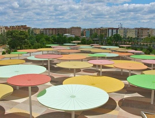 The Centro Abierto de Actividades Ciudadanas project in Spain is an installation of multi-coloured sunshades in the 128,000 square foot space near the central railway station. Shade during the day, light at night, and drainage during rain.