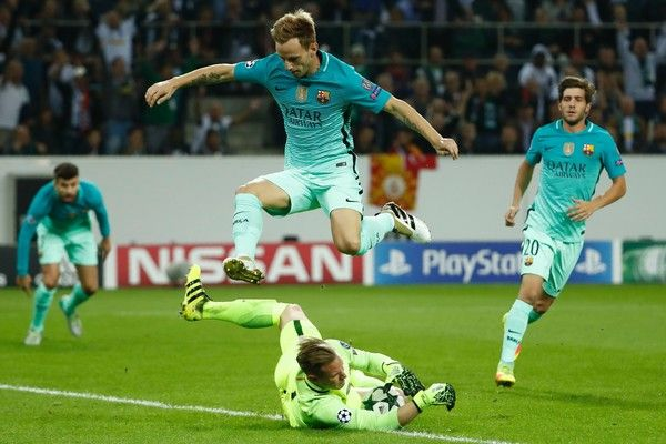 Barcelona's Croatian midfielder Ivan Rakitic jumps over Barcelona's German goalkeeper Marc-Andre Ter Stegen who caught the ball during the UEFA Champions League first-leg group C football match between Borussia Moenchengladbach and FC Barcelona at the Borussia Park in Moenchengladbach, western Germany on September 28, 2016. / AFP / Odd ANDERSEN