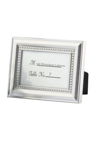 """Enhance each place setting at your resplendent event with these photo frame place card holders! Fill the gleaming metal frame with a place card or a favorite photo. When your guests take this favor home, they can fill the frame with a favorite photo of their own! Features and Facts:  Metal frame is embellished with dainty, beaded design.  Back of frame is covered with black velvet.  Preprinted, ready-to-personalize table card included.  Frame measures 4"""" x 3""""."""