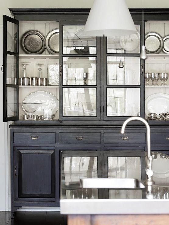 Painted black cabinetry with glass fronts backed with wide white planks. Simple and beautiful for displaying pewter etc.