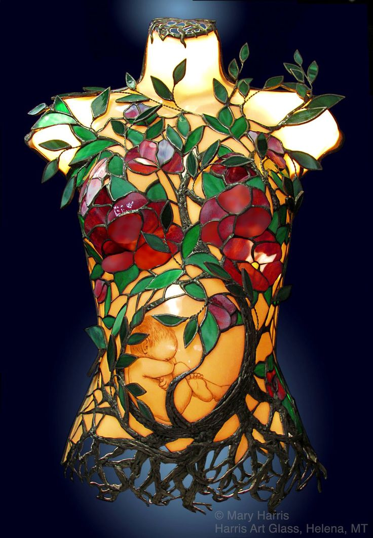 """Tree of Life"" by Mary Harris, Harris Art Glass, Helena, MT. Created to help raise funds for The Florence Crittenton org that works with mothers and babies in Helena, MT. The luminous torso is made of glass and the baby was hand painted onto the belly prior to slumping the glass over a mold. The lovely tree branches, flowers, and roots were then entwined across the slumped glass - Hangs from a section of reinforcing rebar and is lit from within by LED rope lights."