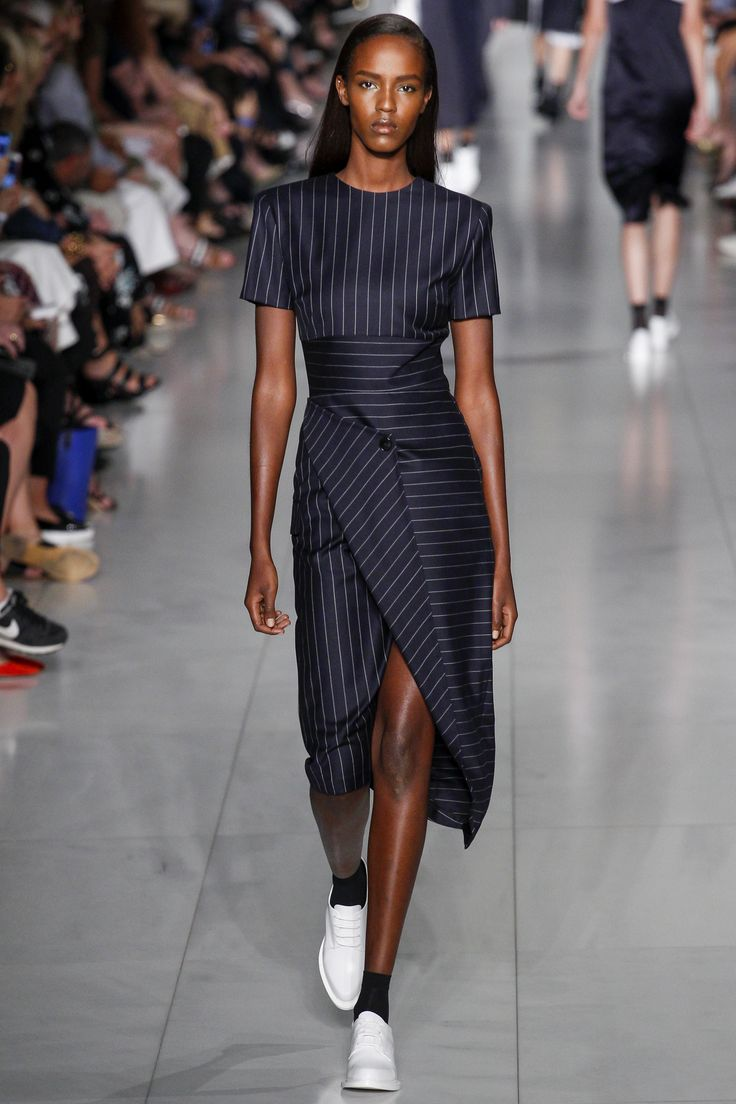 80s power dressing reimagined - strong shoulders, business-like navy pinstripe fabric, but with that split and folded skirt. [Dress by DKNY / Spring 2016 Ready-to-Wear Fashion Show]