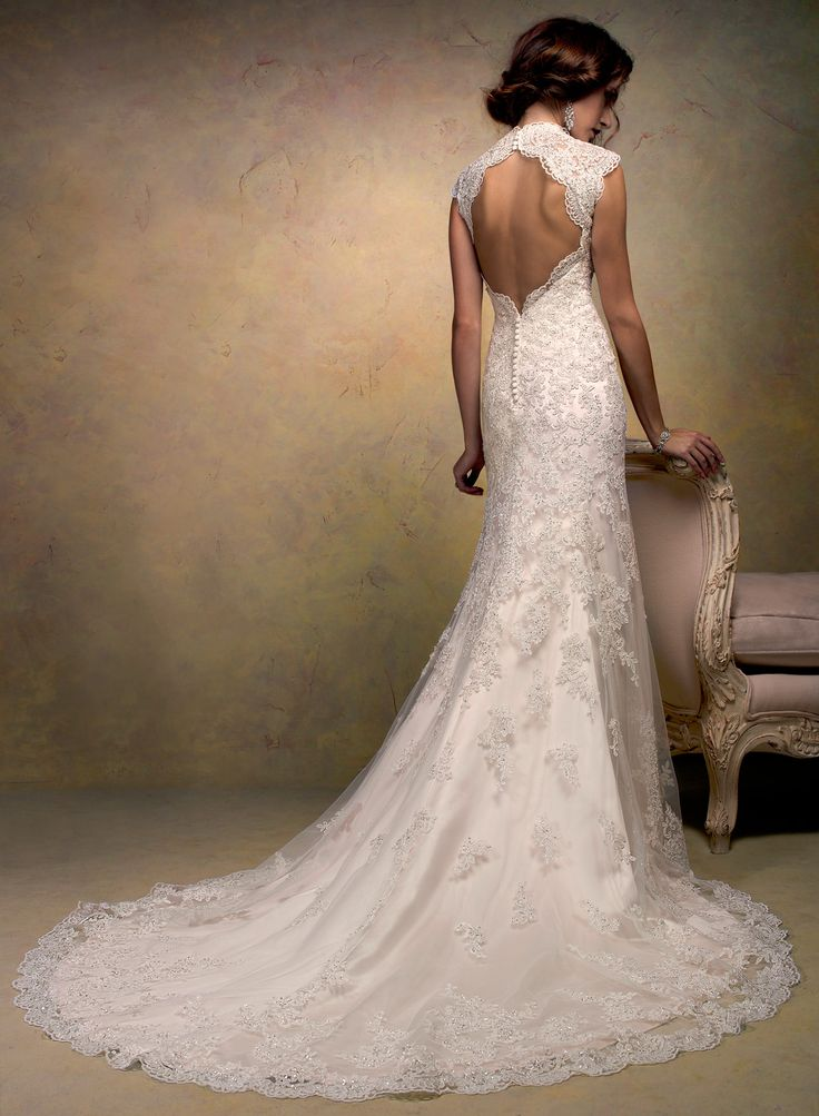 Bernadette - Slim line gown with button over zipper closure. This intricate lace gown features a beautiful high mandarin keyhole back and a fishtail train finished with scalloped edging. Swarovski crystals are delicately sprinkled throughout with rich decorative beading at the empire waist. $1649.00