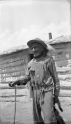 1936 Joseph G. Master's photo of Scabbard Knife, an elderly Native American Sioux man who fought in the Little Bighorn, outside a log cabin, wearing overalls, a hat, and holding a cane, Nayes, Rosebud Reservation, South Dakota.