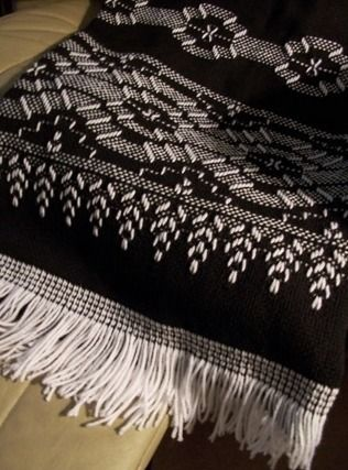 Afghan on black monk's cloth using American School of Needlework design. Weaving by Sandra