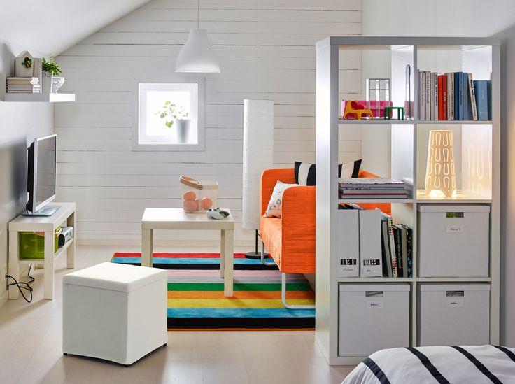 Scaffale bianco usato per dividere la stanza, divano e poggiapiedi con fodere gialle.