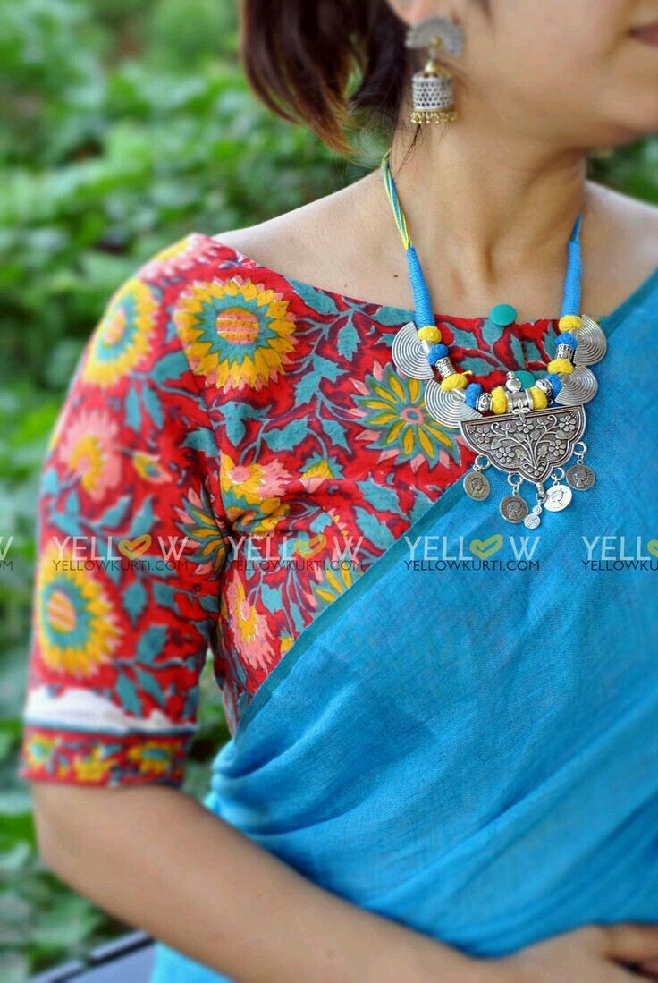 Floral sari blouse with a solid turquoise sari and turquoise/silver necklace.