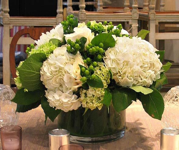 White hydrangeas with green hypericum berries - beautiful centerpiece. Lay it on the table (no base) and have pebbles scattered at the base.