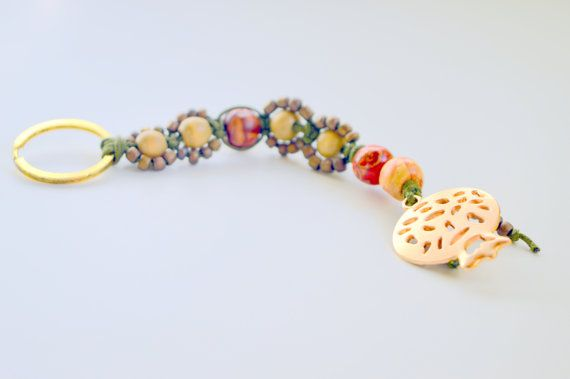It is made from wooden painted beads and seed beads.  From a metal gold metal ring ,hanged green waxed cored beaded with wooden beads with painted flowers , light brown woo... #keychain #brelock #keys #house #car #key #holder #holidays #christmas #ornament #macrame