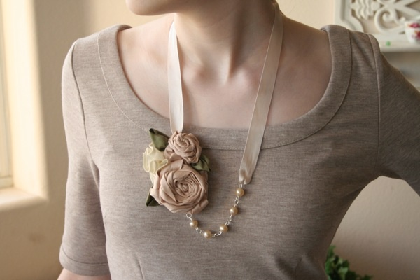 This elegant necklace features a cluster of hand stitched silk roses and leaves, a chain of upcycled pearls, and a satin ribbon to tie around your neck. Made from natural and vintage materials.   Green Bride Guide