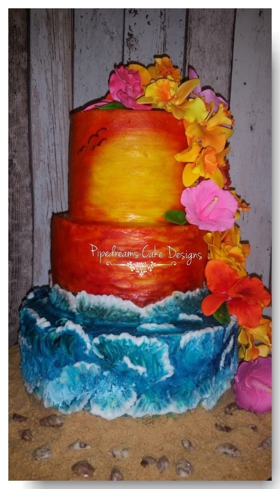 A tropical themed cake with gorgeous tropical sugar flowers cascading down the side, i love the sunset with the ocean waves crashing onto the sand and the scattered sea shells.