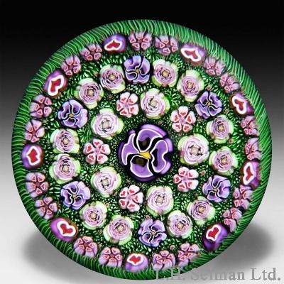 """Parabelle Glass 1998 concentric millefiori moss ground paperweight. Three concentric rows of assorted Clichy-style roses, pansies and heart canes ring a large central purple pansy, on a lovely red heart/moss ground. Edition No.3 of a limited edition of 10. Signed/dated. Diameter 3 3/16"""". www.theglassgallery.com (this picture should be rotated 45 degrees to the right)"""