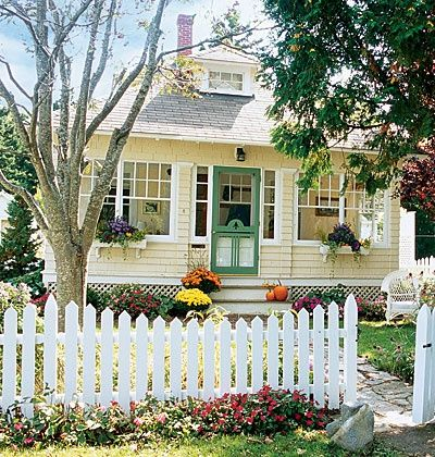 Yellow house, white trim, green door with picket fence - cute.  I would want a blue door