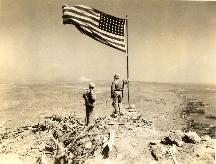 Two Marines assess the area while standing next to the raised flag on Mount Suribachi, 1945. LST's lined up along the assault beaches to the right, the rest of Iwo Jima stretches out in the distance to the left. This photo was taken by Lt. James T. Dockery, 4th Marine Division.