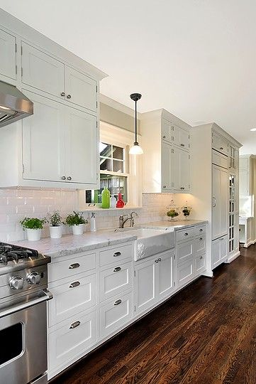 White cabinetry + Stained oak floors + pendant + subway + marble