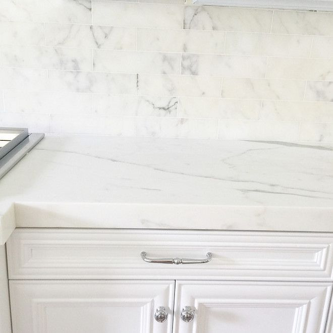 The designer used Calcutta marble, 3″x 12″ subway tiles with white grout for the kitchen backsplash. For the island and counters she chose a 2″, honed Calcutta marble with a clean, mitered edge. Restoration Hardware pulls and knobs look beautiful with the marble.
