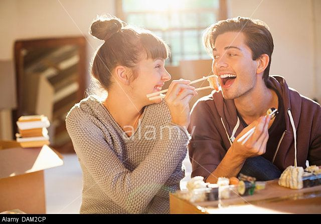 Couple eating sushi together in new home © Bill Cheyrou / Alamy