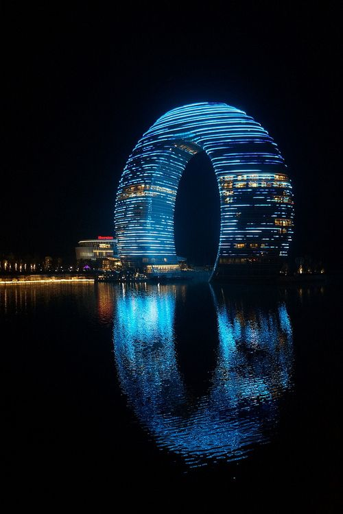 Futuristic building with neon lighting around the arch makes it stand out. Awesome how the reflection of the water makes a complete shape with the building