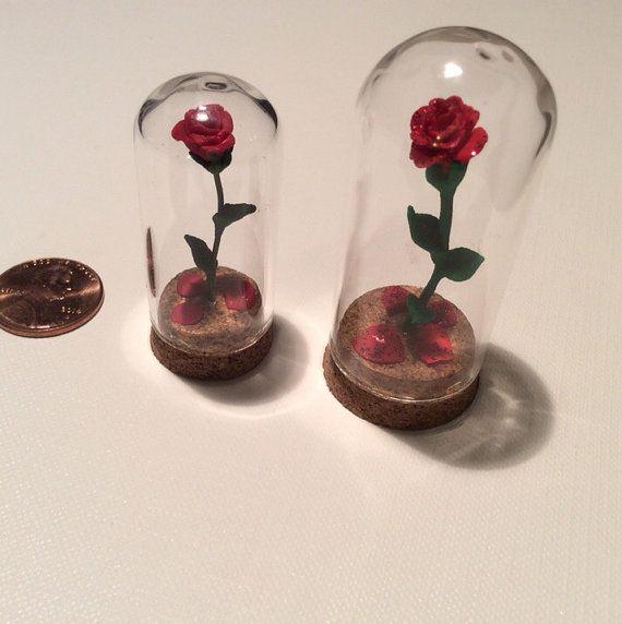 Ces cloches roses fantaisistes sont inspirés par les classiques de Disney la belle et la bête et ferait un grand ornement Bureau pour tout fan de Disney !  Cette liste est pour mini cloche enfermé rose. La grande cloche rose est 2 de haut, et la plus petite cloche est environ 1 1/2 de haut. Les roses sont faites dune argile de polymère durable et tiges sont un fil floral vert. Les roses sont ancrés dans les bouchons, qui sont collées solidement sur les bocaux de verre bombé. Chaque cloch...