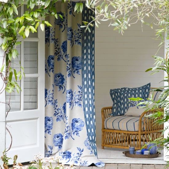 Relaxed garden summer house - Couple up complementary patterns to make a statement at a window. Here a rose print and ikat weave have been combined to create a stylish double-sided curtain.