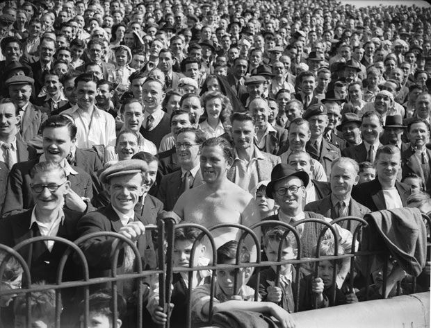 16 April 1949: Crowds watch a Chelsea versus Derby County football match at Stamford Bridge during an Easter heatwave in London