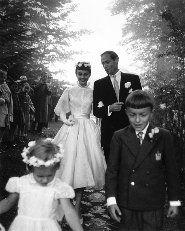 Audrey Hepburn and Mel Ferrer - 24th of September 1954. The dress was designed by Pierre Balmain and was iconic because of its short length. Instead of wearing a veil, Audrey wore a halo of flowers. She looks fabulous!