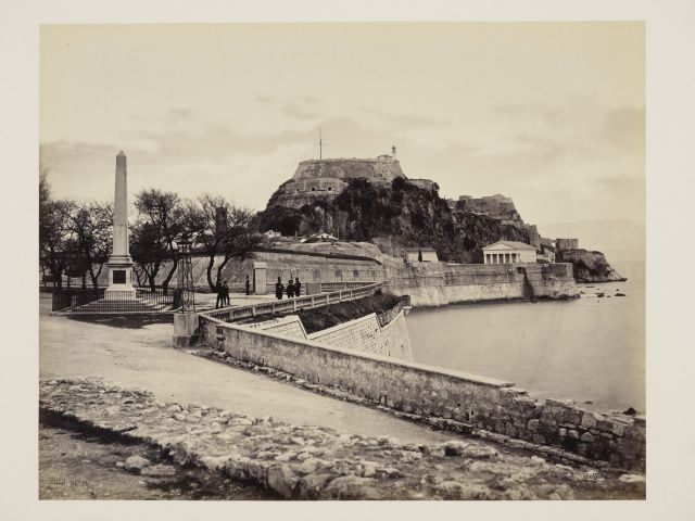 Corfu The Citadel - English Church and Obelisk to Sir Howard Douglas [Corfu]  24 Feb 1862. View of the Citadel on hillside, centre, with sea on right visible over sea wall. Left, obelisk erected to memory of Sir Howard Douglas, Lord High Commissioner of the Ionian Islands (1835–1840). St. George's Church can be seen on the right of the view. Acquired by the Prince of Wales (later King Edward VII), 1862