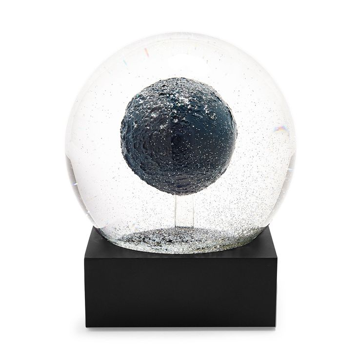 Inspired by lunar surfaces, this snow globe imagines the moon as a crystal orb suspended amid glittering stars of confetti. Each globe melds sophistication with whimsical delight.