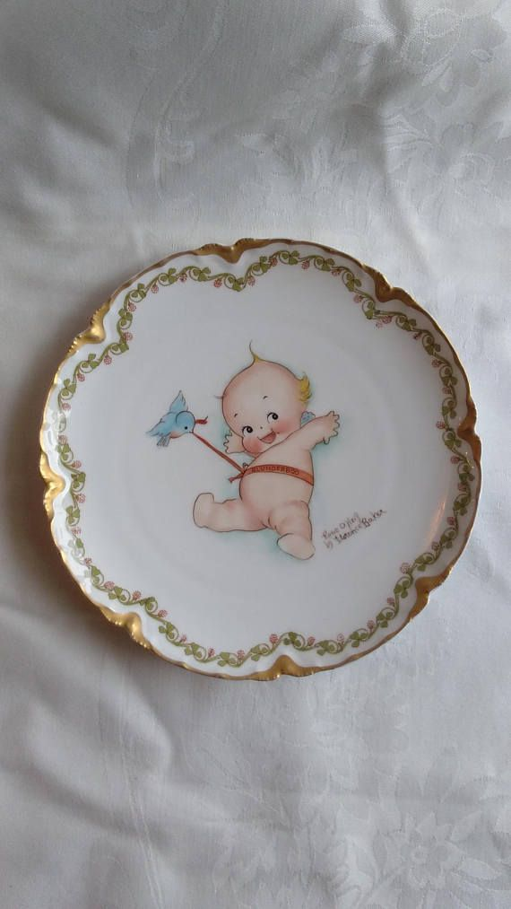 Darling Kewpie Blunderboo baby painted by Florence Baker in the style of Rose ONeill on a French Limoges china plate. Smiling baby with blue bird pulling on the Blunderbo sash wrapped around baby. Clover leaves and flowers border the plate with a gold rim. 7 1/2 inches in diameter 19.5