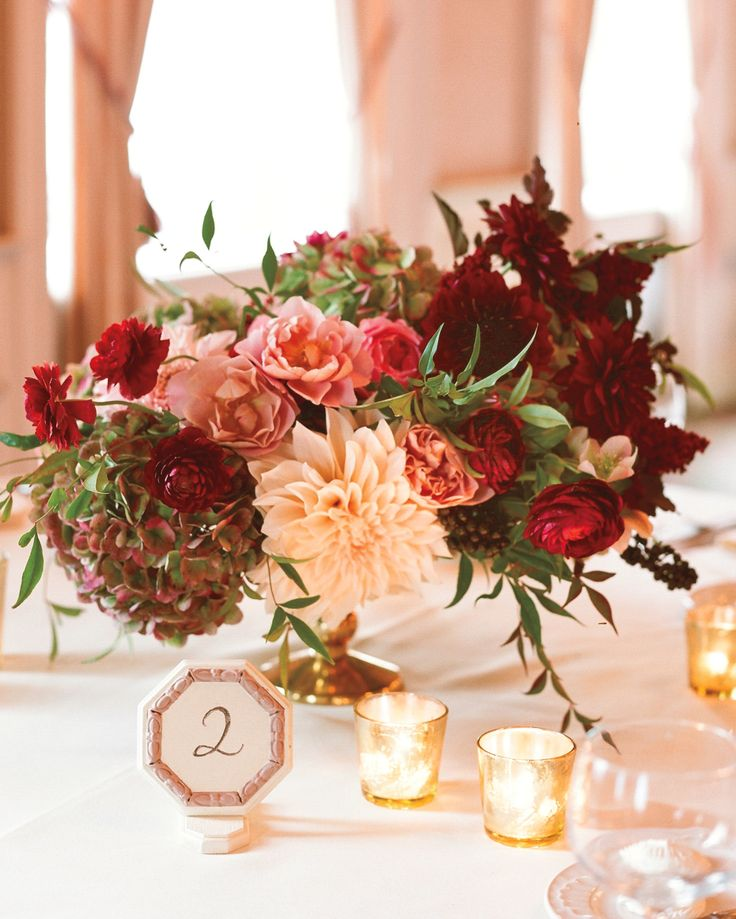 dahlias, ranunculus, roses, hydrangea in shades of ruby red and soft pinks, arranged in gold pedestal vases, and surrounded by gold mercury glass votive holders