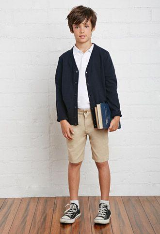 Estos son uniformes para los estudiantes de una tienda de Forever 21. El uniforme de niño tiene una camisa blanca, abrigo negro y  pantalones cortos caqui. Debe ser su primer día de escuela.