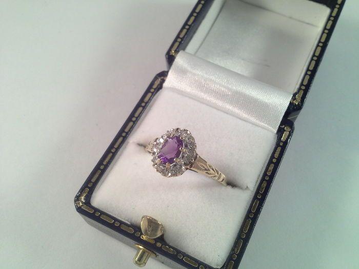 Klassieke geel gouden ring met amethist en diamant  Deze elegante geelgouden ring is gezet met een ovaal geslepen natuurlijke amethist. Daar omheen zijn 8 diamanten gezet. De stenen zijn gezet in wit goud. De bovenkant van de ring is 1 cm bij 8 mm. Amethist 1 x 6 bij 4 mm ovaal geslepen Diamant 8 x 0.01 ct briljant geslepen H /VS Merken : meesterteken GJ rozet 375 voor 9 kt goud ( beneden het wettelijk goudgehalte in sommige landen ) anker. Ringmaat : 17 75/56 Weight: 1 69 gr Aangetekende…