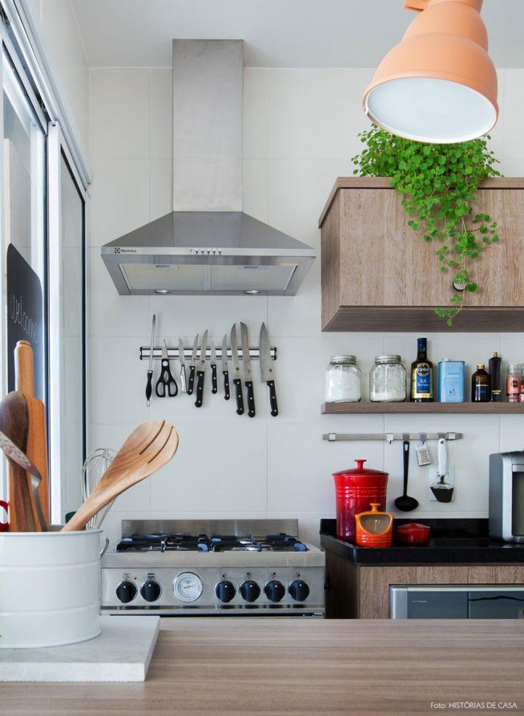 Decoração de cozinha aberta, com coifa e facas a mostra graças ao painel com imã. A planta em cima do armário traz ainda mais vida ao ambiente.