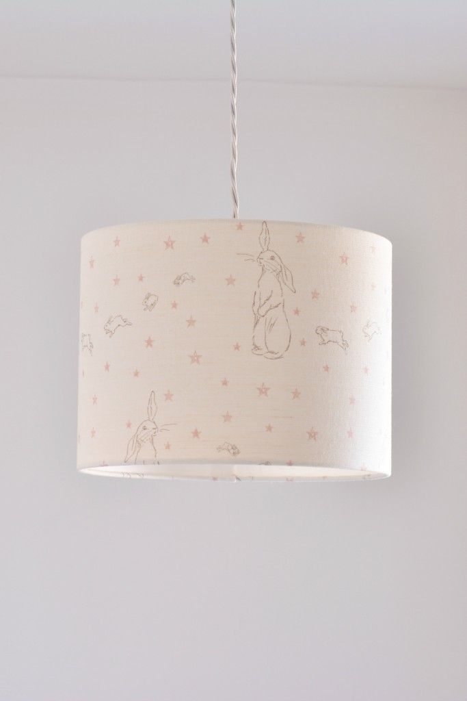 A gorgeous drum lampshade handmade in this adorable Peony & Sage Rabbit All Star linen union blend on oyster white base cloth, featuring a vintage original rabbit and her little ones following behind. Available to order in Pink Star or Blue Star options to fit ceiling pendants or lamp bases. All lampshades are lovingly handmade...