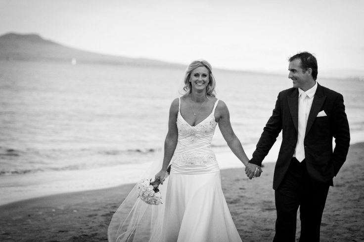 Bride and groom walk along the beach after their wedding at home at Milford beach, Auckland. Black and White.  beguiling fine art family photographs for the walls of the most discerning clients homes. We specialise in wedding and family portrait photography, and supply prints on the highest quality media, framed in beautiful conservation standard frames. We are a high end studio located in the beautiful city of Auckland, New Zealand.