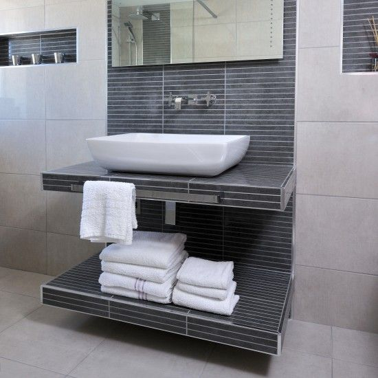 Grey and white modern bathroom | Bathroom storage ideas | Ideal Home | housetohome.co.uk | This sleek bathroom has a neutral palette of white, grey and cream. A floor-to-ceiling tiled splashback behind the basin creates a focal point. The shelves beneath the basin have also been tiled to keep the look streamlined. Splashback = Bathrooms2buy. Similar taps = Homebase