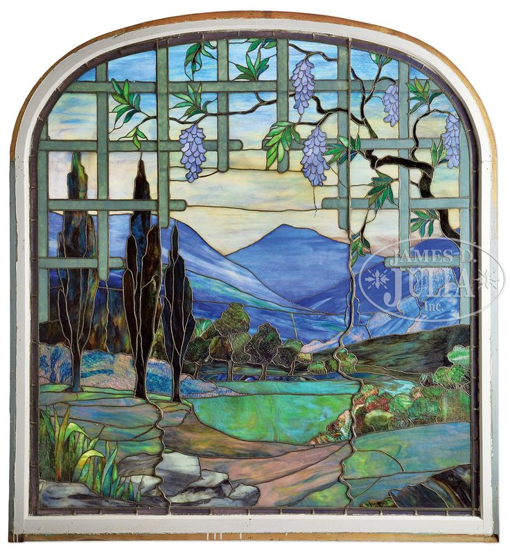 Unsigned, byt attributed to Tiffany. Leaded glass window has country scene with trees, rocks and grasses in the foreground looking through a wisteria trellis to blue and white mountains in the distance. All set against an amber shading to blue sky. The window is plated in two layers in sections to add depth of color. The trees are done in mottled green, brown and red granite glass. . SIZE: 77-1/2″ t x 70-1/2″ w including what appears to be the original wooden frame.
