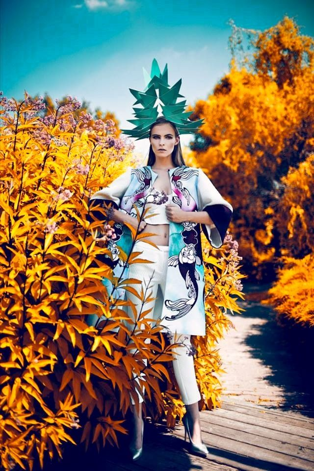 Although there is a lot going on in this image, the colors work well together. The golden foliage creates a very nice balance with the turquoise o the sky and the model's geometric headpiece. I love the interest her headpiece creates as well. It, combined with her pose, give s the illusion that the model herself is a building or goddess of some import.