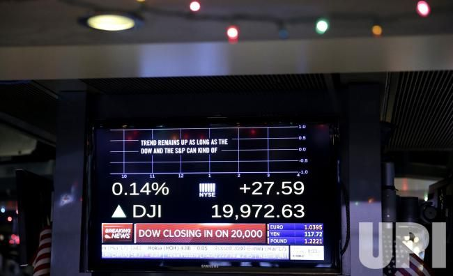 A monitor on the floor of the NYSE shows the Dow Jones Industrial Average up 27 points after the opening bell at the New York Stock…