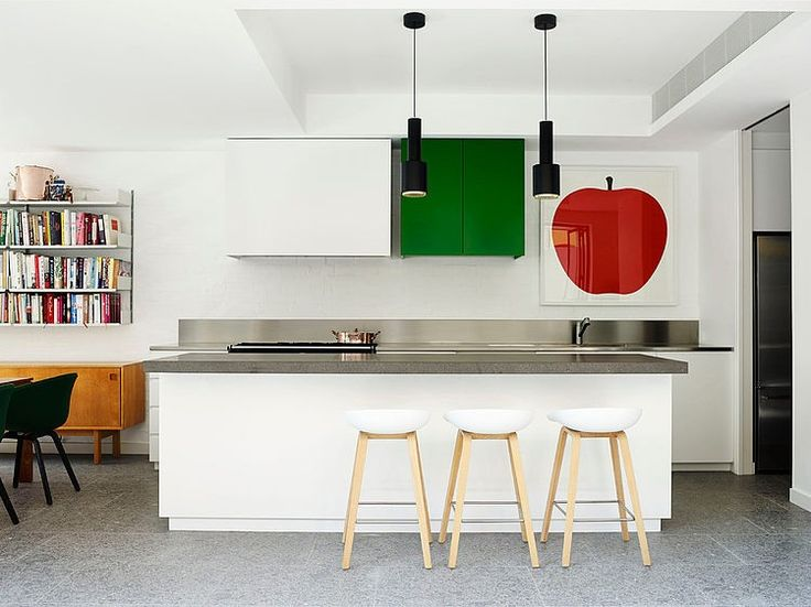 Apple print artwork in minimalist kitchen. Stainless steel and grey stone benchtops, grey floor tiles. Modern black pendant lights. White and wood bar stools.