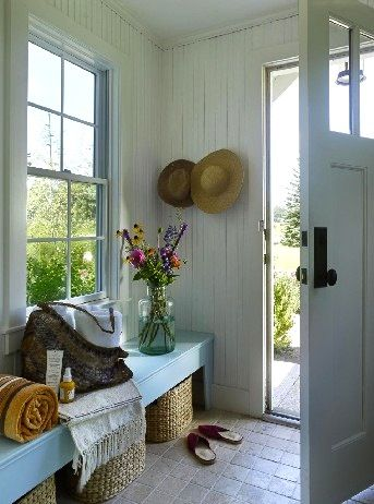 bench by the front door with baskets and hanging hats. more rustic wood bench though