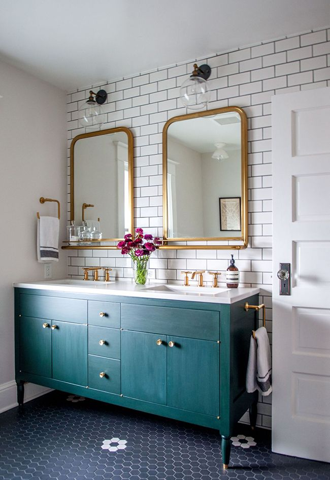 bathroom refresh: dark teal wash finish on bathroom vanity with brass hardware, framed mirrors and vintage hex tile floors in black with white accents.