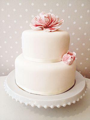 Vit bröllopstårta med rosa blommor.